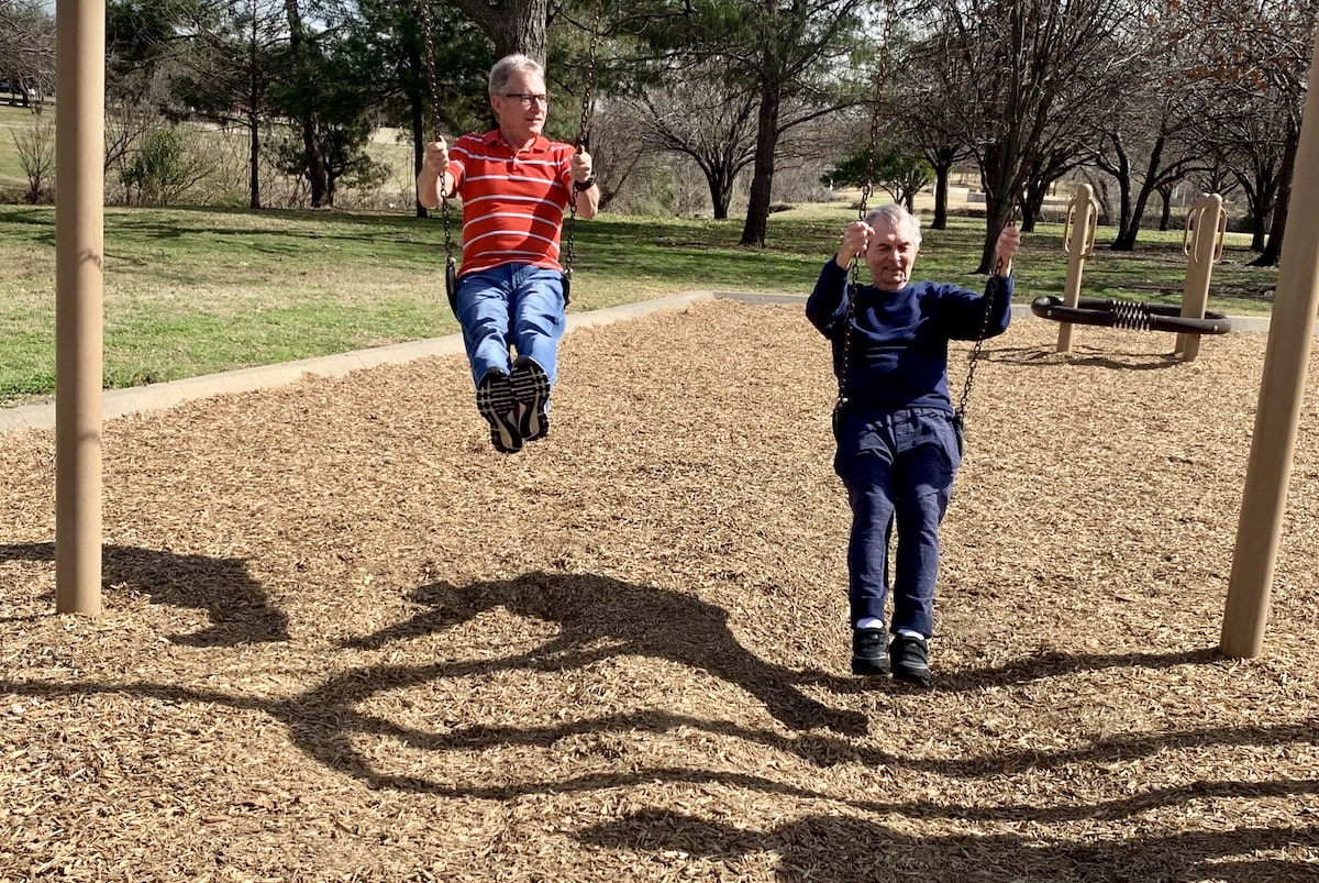 Elderly men playing on swing set