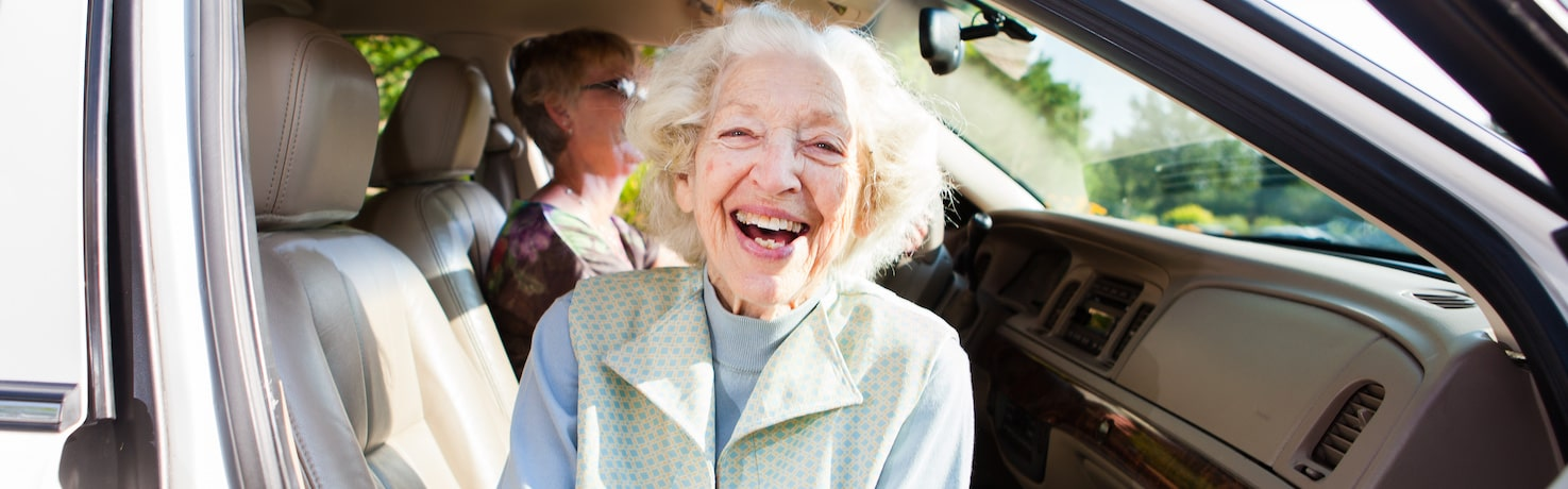 Smiling elderly woman in automobile