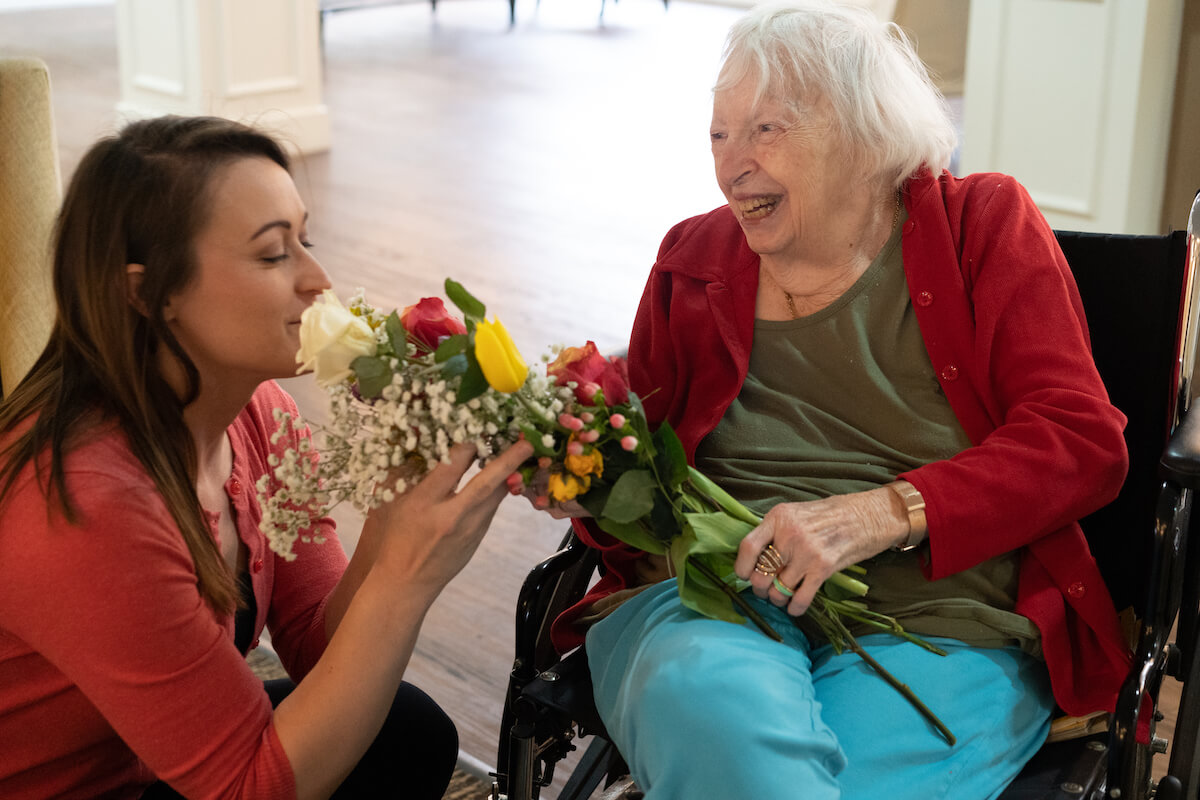 caregiver smelling flowers giving to a residence