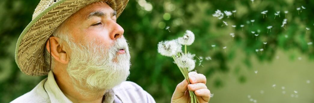 man blowing on a flower